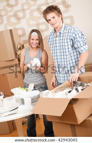 Moving house: Young couple unpacking kitchen dishes, pots, pans, in new home