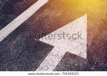 Moving in the right direction, white arrow symbol as traffic sign on asphalt road for motion directing toward the successful future represented by the bright sunlight