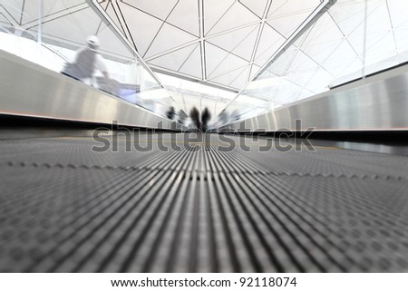 moving passenger rushing through an escalator in airport terminal