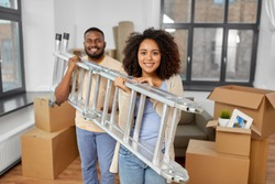 moving, people, repair and real estate concept - happy african american couple with ladder at new home