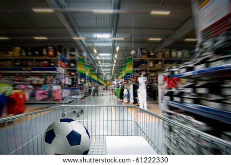 Moving shopping cart in the supermarket interior.