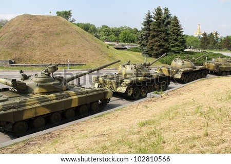 Moving tanks column against city trees and background