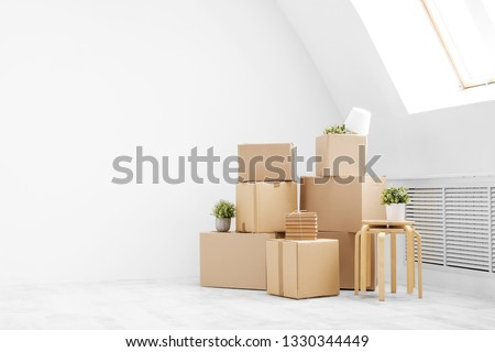 Moving to a new home. Belongings in cardboard boxes, books and green plants in pots stand on the gray floor against the background of a white wall. Concept relocation. #1330344449