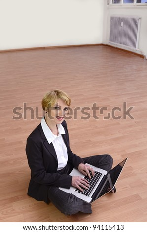 Moving to new office: Businesswoman with laptop in empty room