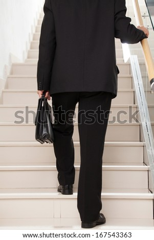 Moving up. Cropped rear view image of man in formal wear moving up by stairs