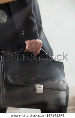 Moving up. Cropped side view image of man in formal wear carrying a briefcase and moving up by stairs