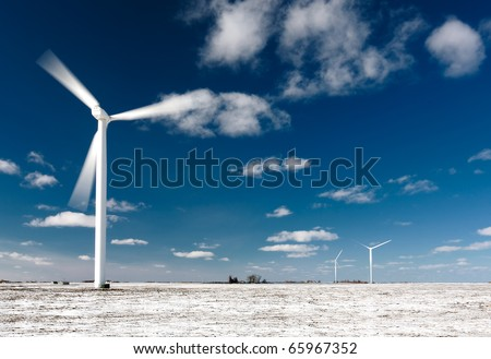 Moving wind turbine blades in snow covered winter field.