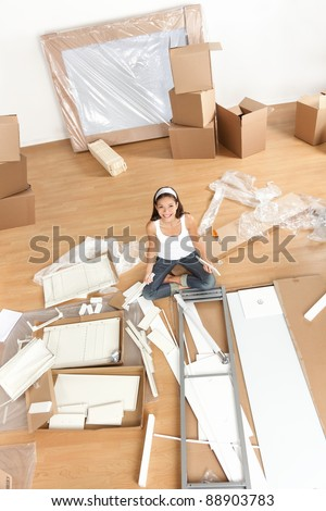 Moving woman in new home sitting on floor unpacking and assembling furniture. Multiracial Asian Caucasian young woman.