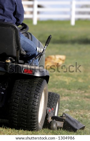 Mowing a large area with a riding lawnmower (shallow focus).