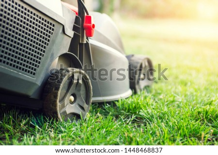 Mowing a lawn with a lawn mower. Lawn mowers cut grass. Garden work concept background. #1448468837