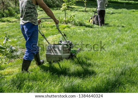 Mowing green grass in the park with a lawnmower #1384640324