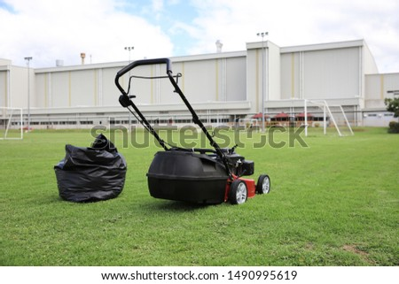 Mowing lawns, Lawn mower on green grass #1490995619