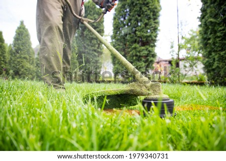 Mowing the grass with a lawn mower. Garden work concept background. Сток-фото ©