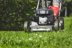 Mowing the grass with a lawn mower in garden at spring. Mowing lawn at sunny day.