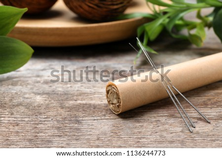 Moxa stick with needles for acupuncture on wooden table
