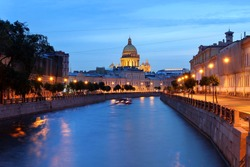 Moyka canal in downtown Saint Petersburg, Russia at twilight with the dome of Saint Isaac Cathedral in the skyline.
