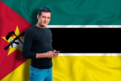 Mozambique flag on the background of the texture. The young man smiles and holds a smartphone in his hand. The concept of design solutions.