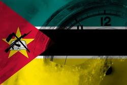Mozambique, Mozambican flag with clock close to midnight in the background. Happy New Year concept