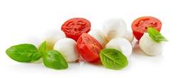 Mozzarella cheese balls with tomato and basil isolated on white background