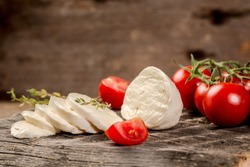 Mozzarella cheese, basil and tomato cherry on slate stone board, copy space. Ingredients for Caprese salad. Free space for your text.
