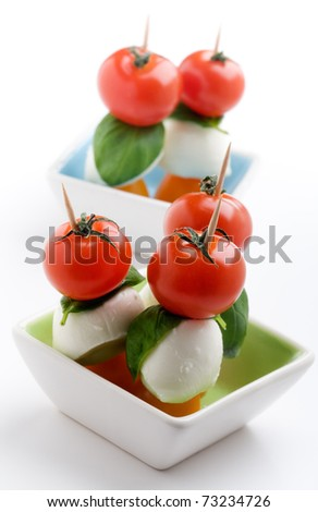 Mozzarella, tomatoes and fresh basil leaves on white background