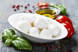 Mozzarella with tomatoes and basil leaves  on Wooden background