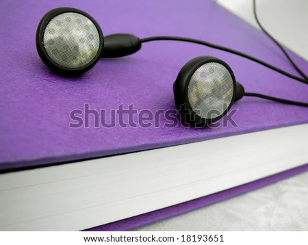 mp3 player ear buds and reading book - stock photo