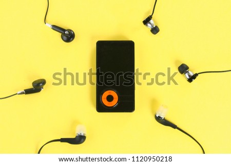 MP3 Player with Headphones on pastel yellow background. Minimalism.