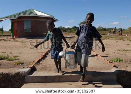 MPHANDULA, MALAWI – CIRCA MAY 2007 : Loal kids carry water can in 'Raising Malawi' orphanage circa May 2007 in Mphandula. The orphanage is a charity non-profit organisation, co-founded by Madonna.