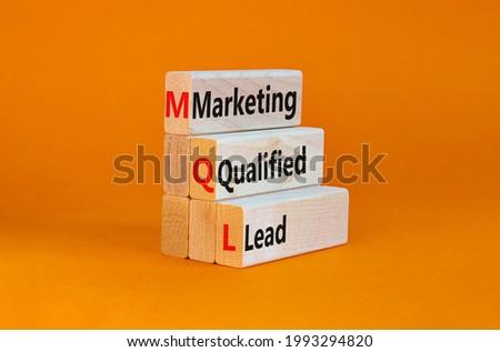 MQL marketing qualified lead symbol. Wooden blocks with words 'MQL marketing qualified lead'. Beautiful orange background. Business and MQL marketing qualified lead concept. Copy space.