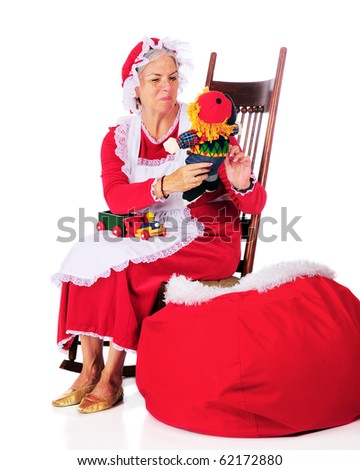 Mrs. Claus checking out the toys as she loads them into Santa's sack.  Isolated on white.