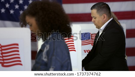 MS Hispanic man at polling station, votes in a booth with young Hispanic woman in foreground and blonde Caucasian woman behind and US flag in background