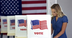 MS Young blonde woman casts votes at booths in polling station with US flag.