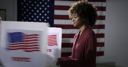 MS Young mixed-race woman ready to vote with blurred voting booth in foreground, being removed. Symbol of disenfranchisement with US flag backdrop