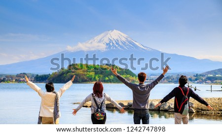 Mt diamond fuji with snow and flower garden along the lake walkway at Kawaguchiko lake in japan, Mt Fuji is one of famous place in Japan. People hands up and looking far away.