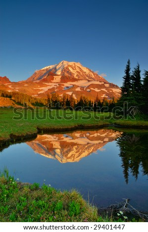 Mt. Rainier seen from Spray Park Meadows reflected in a tarn at sunset