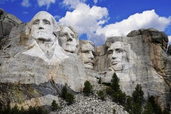 Mt. Rushmore National Memorial Park in South Dakota with bright blue sky in background. Sculptures of former U.S. presidents; George Washington,Thomas Jefferson,Theodore Roosevelt and Abraham Lincoln.
