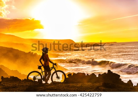 MTB cyclist mountain biking woman cycling looking at view on bike trail on coast at sunset. Person on bike by sea in sportswear with bicycle enjoying healthy active lifestyle in beautiful nature.