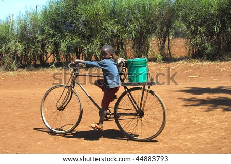 MTITO ANDENI, KENYA - JULY 13 : A child carries water with a bicycle July 13, 2009 in Mtito Andeni, Kenya. Thanks various humanitarian organizations, the people of this village can drink water.