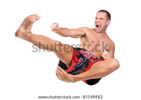 Muay Thai fighter jumping isolated on white background. Sportive man jumps in martial kick. Fighting man jumps in combat jump. Attack kick flying man. Aggressive attacker in a combat sport Muay Thai.