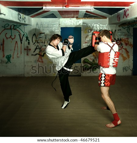 Muay Thai fighter practicing his blocking technique during a practice round with a Wing Chun fighter - stock photo