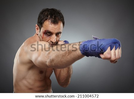 Muay thai or kickbox fighter with bruises and blood on his face, throwing a direct punch