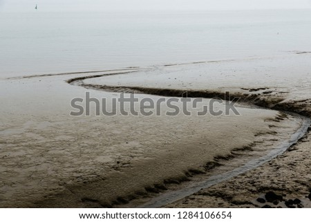 Mud grooves at the beach and shallow waters of the Atlantic Ocean in Lisbon, Portugal on a foggy day.