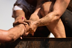 Mud race runners.Couple hold hands,help when overcoming hindrances mud