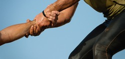 Mud race runners. Couple hold hands,help when overcoming hindrances mud