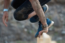 Mud race runners,participant jumps over obstacles