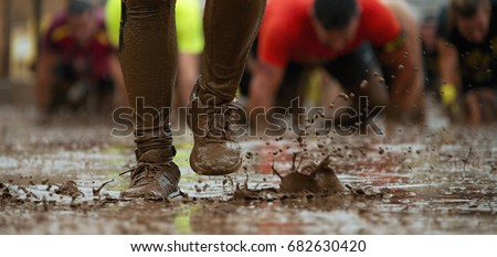 Mud race runners passing under a barbed wire obstacles during extreme obstacle race,detail of the legs #682630420