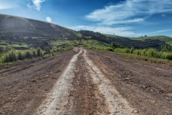 Mud road with tire marks runs through green valley in Malanje. Angola. Africa.