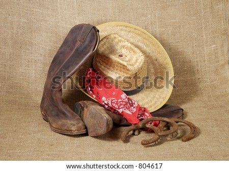 Muddy cowboy boots, straw hat , bandanna and old horseshoes on a burlap background.