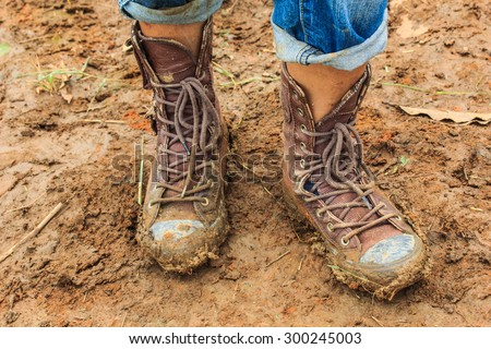muddy feet-shoes - walking through the mud,Dirty hiking boots at mountain landscape background. Durable and hard duty footwear concept. #300245003